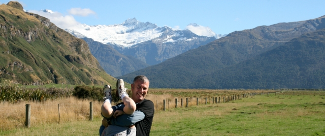 The Author and his uncooperative son before Mt Avalanche and Mt Aspiring (above cloud to right)